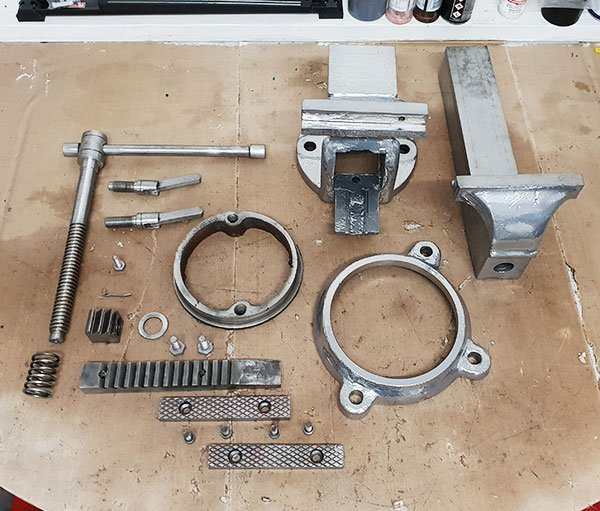 Chrome powder coated vice parts laid out on the work bench before reassembly.