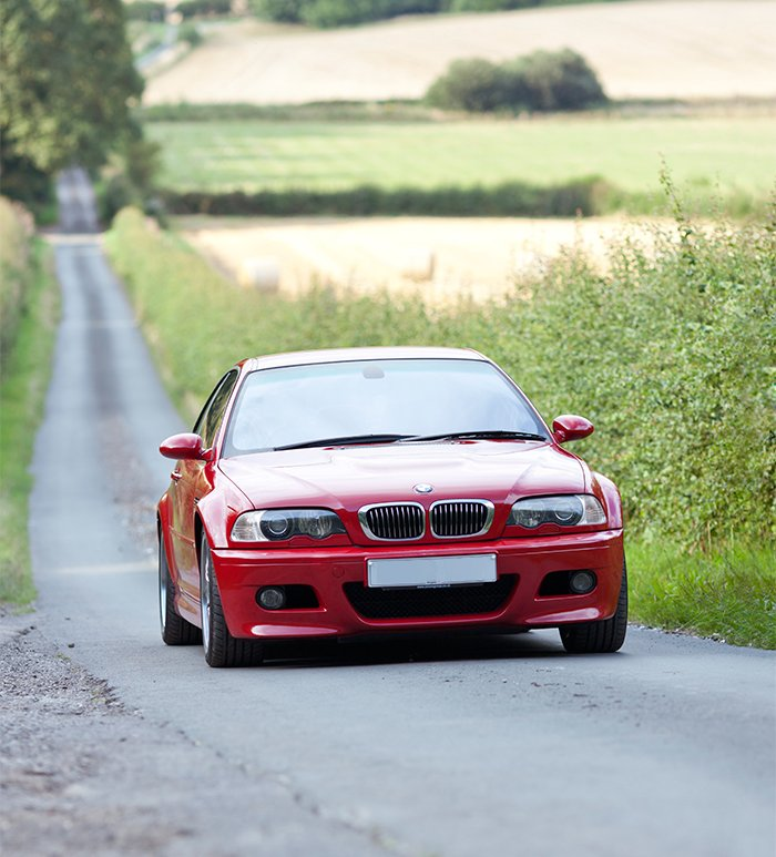 Imola Red BMW E46 M3 blasting up a British B road.