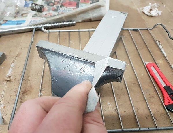 Removing the masking tape from the freshly powder coated metal parts.