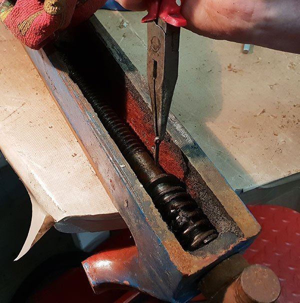Removing the R clip that holds the threaded bar into the vice with needle nosed pliers.