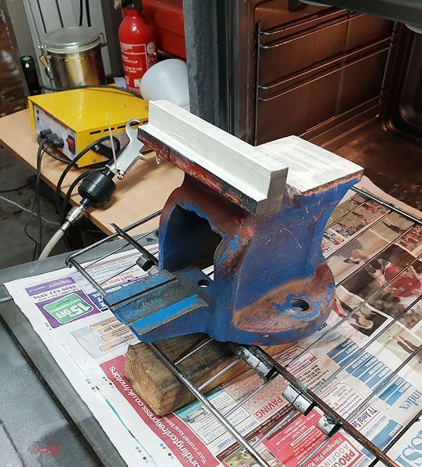 Heating the main body of the vice in the oven before powder coating.