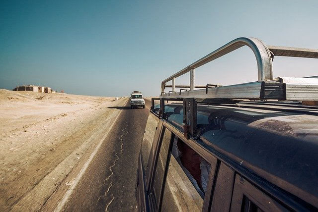 Land rover Defenders travelling on the road in the middle east.