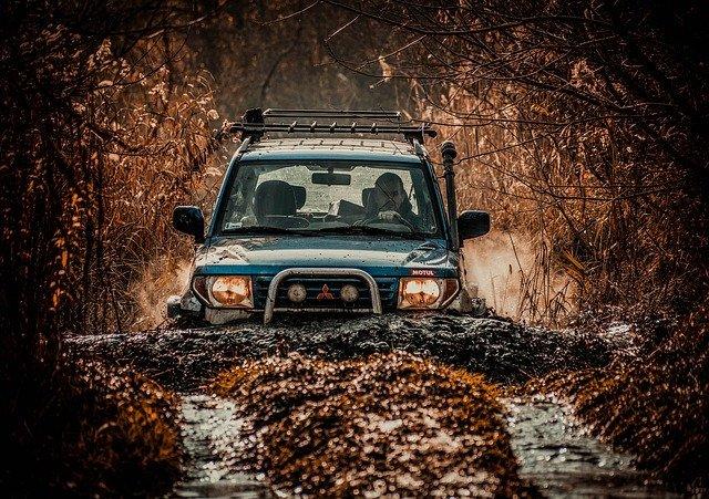 Mitsubishi off-roader climing a muddy hill.