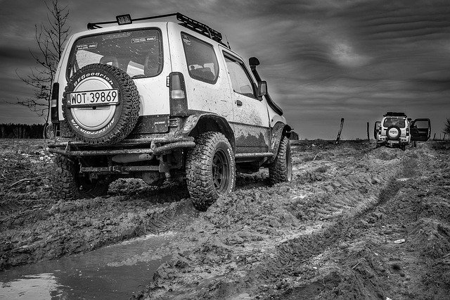 Pair of Suzuki Jimny off-roaders being driven through thick mud.