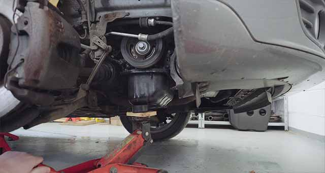 Using a jack to support the engine while the engine mount is removed.